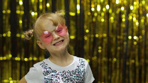 Cover Image for Child Smiling, Looking at Camera. Girl in Pink Sunglasses Posing on Background with Foil Curtain