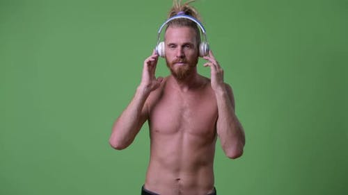 Handsome Muscular Bearded Man with Dreadlocks Listening To Music Shirtless