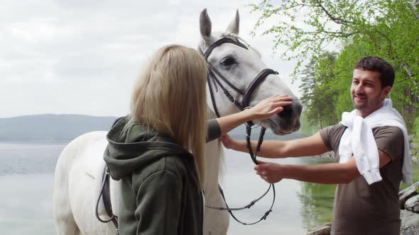 Thumbnail for Couple Petting Beautiful Horse by the Lake
