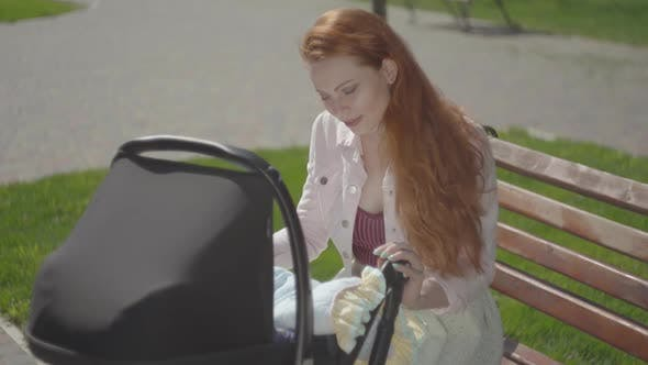 Thumbnail for Portrait Red-haired Woman Playing with Her Child Sitting on the Bench. The Stroller Standing Near