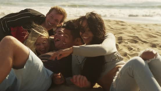 Thumbnail for Group of friends laying down on the sand at the beach laughing