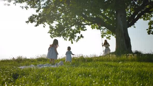 Thumbnail for Two Little Sister Girls Run Across a Clean Green Field To Their Mother, Swinging on a Swing.