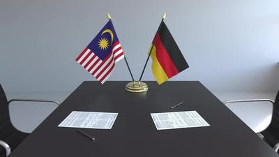 Flags of Malaysia and Germany and Papers on the Table
