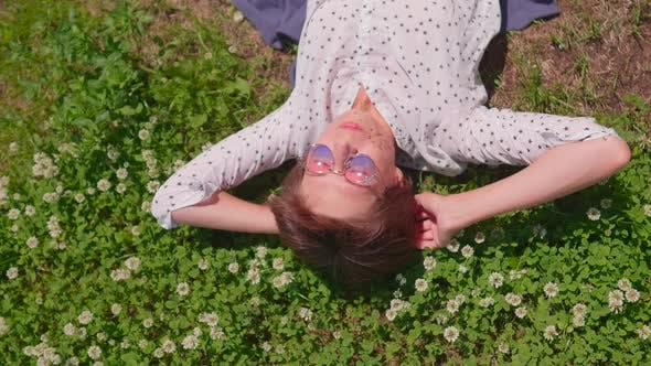Top View on Woman with Colorful Sunglasses Lying on Lawn in Urban Park and Enjoys Flowers