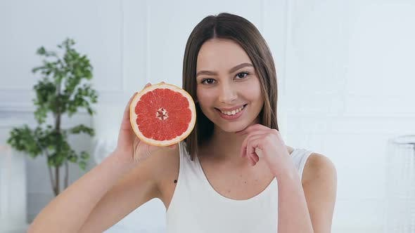 Cover Image for Handsome Caucasian Woman Posing with Half of Grapefruit