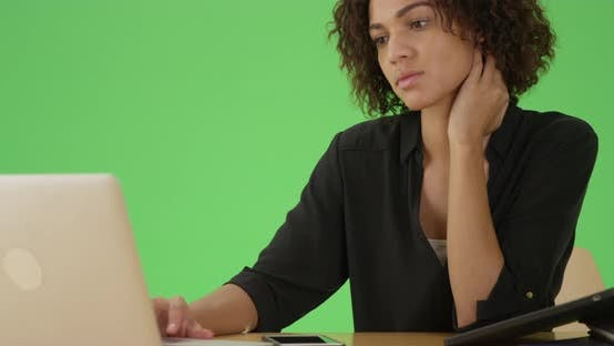 Thumbnail for A young african American woman uses her laptop at her desk on green screen