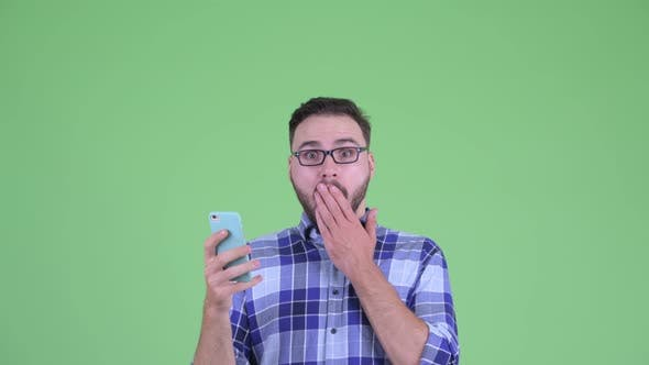 Thumbnail for Happy Young Bearded Hipster Man Using Phone and Looking Surprised