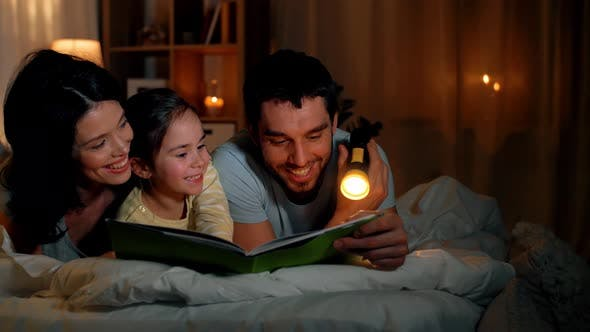 Thumbnail for Happy Family Reading Book in Bed at Night at Home