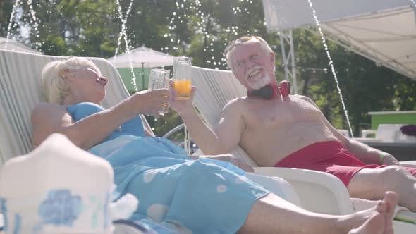 Cover Image for Elderly Positive Couple Lying on Sunbeds Near the Pool Drinking Juice