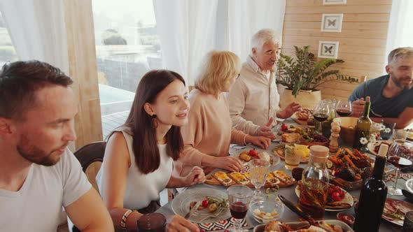 Thumbnail for Large Family Enjoying Festive Dinner and Chatting at Dining Table