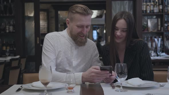Thumbnail for Blonde Bearded Man and Brunette Woman Sitting in the Restaurant at the Table