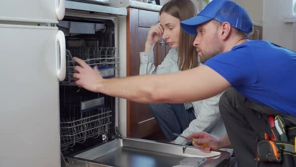 Plumber Repairs the Dishwasher and Talks to the Housewife