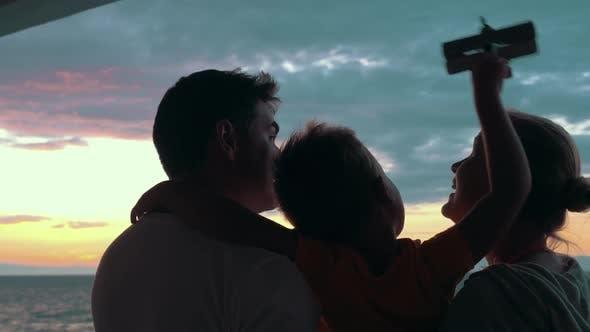 Happy Family with Child Enjoying Sunset