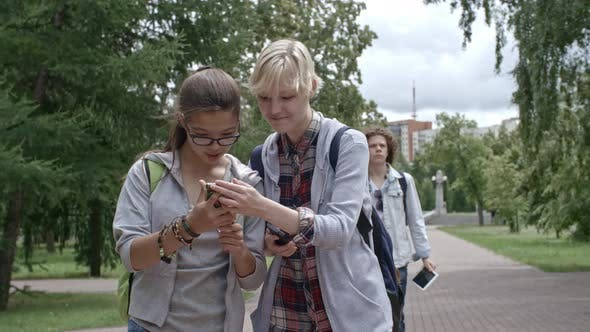 Cover Image for Teen Girls Using Smartphones while Walking in Park