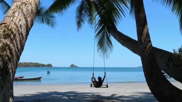 Thumbnail for Man Swinging on a Paradisiacal Beach Under Palm Trees