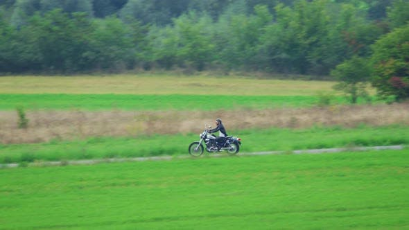 Cover Image for Man riding motorcycle on rural road