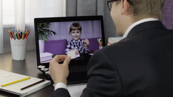 Thumbnail for Man Teacher Makes Video Call on Laptop with Children Pupil. Distance Education