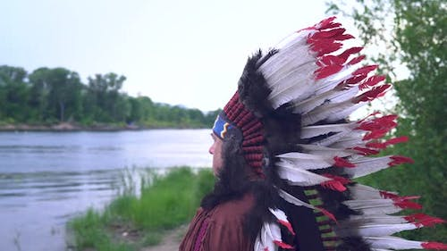 Old Native American Indians Stands on the Background of the River Background of the River