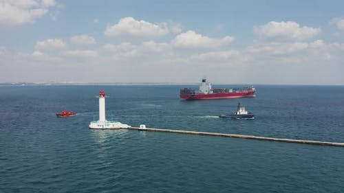 Shipping containers Cargo Vessel passing Lighthouse