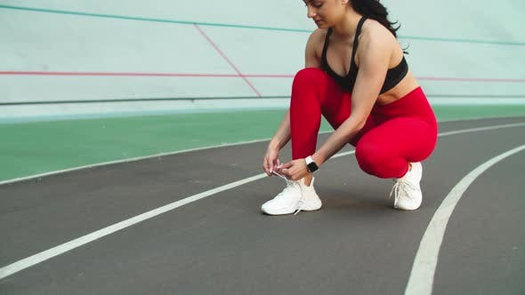 Thumbnail for Sport Woman Lacing Up Sneakers for Workout on Track. Woman Runner Tying Up Shoes