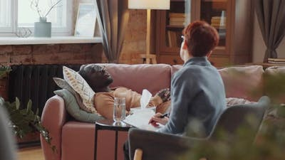 Black Man Lying on Couch and Talking with Psychologist