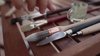 Closeup Painting Brushes and Knives on Wooden Table with Female Caucasian Hand Taking Paintbrush in