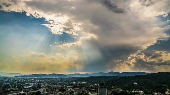Thumbnail for Sunrays Penetrating Clouds in Heavenly Sky Above Mountain Resort City, Timelapse
