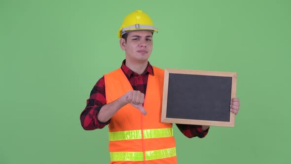 Cover Image for Stressed Young Multi Ethnic Man Construction Worker Holding Blackboard and Giving Thumbs Down