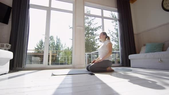 Woman Kneeling on Yoga Mat and Meditating