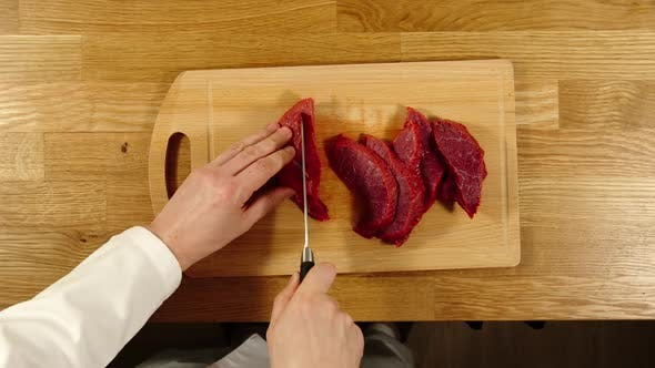 Thumbnail for Cook Takes Knife And Cuts Beef Into Slices And Then Into Pieces