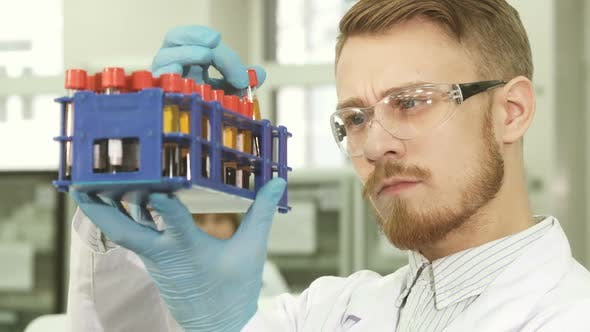 Thumbnail for A Serious Laboratory Assistant Carefully Examines Each Tube Individually