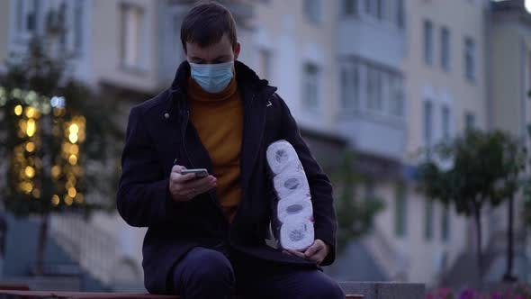 Thumbnail for Men Sits on Bench in Medical Mask with Toilet Paper and Smartphone During the Second Wave Quarantine
