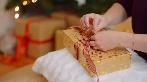 Midsection Of Woman Tying Ribbon On Christmas Present
