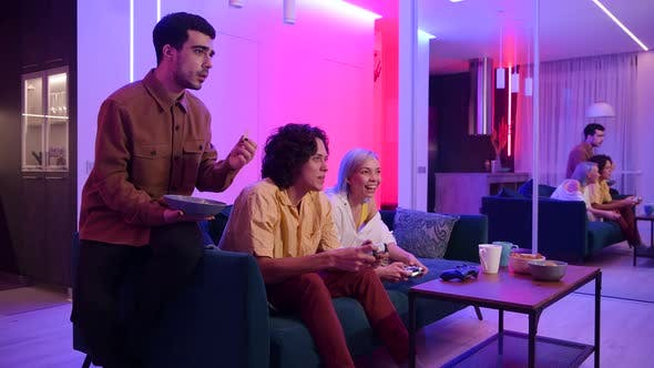Thumbnail for Young Friends Play Video Games While Sitting on a Couch in a Living Room