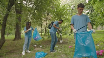Multiracial Group of Young Volunteers Using Litter Sticks Outdoors