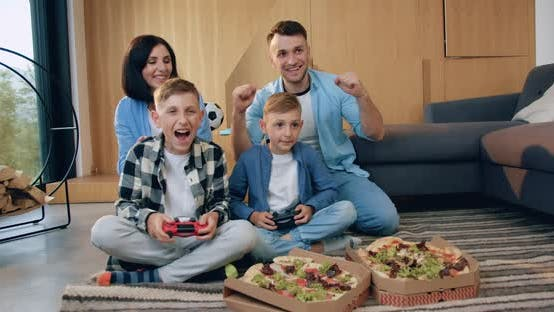 Thumbnail for Parents Encouraging their Two Sons which Playing Video Game