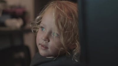 Three year old girl watching TV at home