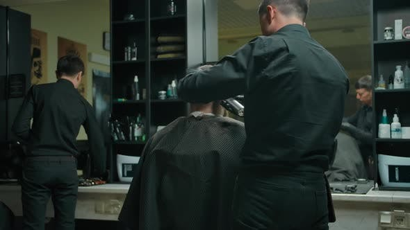 Middle Shot From the Back of a Client Haircut By a Hairdresser