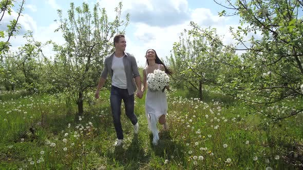 Thumbnail for Happy Couple Running Holding Hands in Fruit Garden