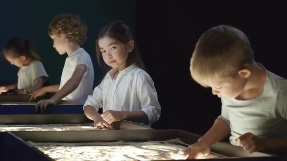 Thumbnail for Adorable Asian Girl Smiling in Sand Animation Class