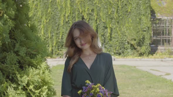 Thumbnail for Portrait of Playful Cute Young Woman Holding Bouquet of Wild Flowers Looking at Camera While