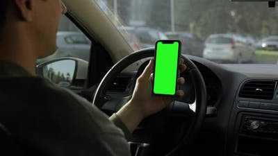 Man in a sweater sitting in the car and watching iPhone with green screen.