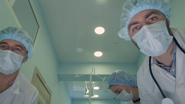 Thumbnail for Group of surgeons looking down at patient on the way to operation room