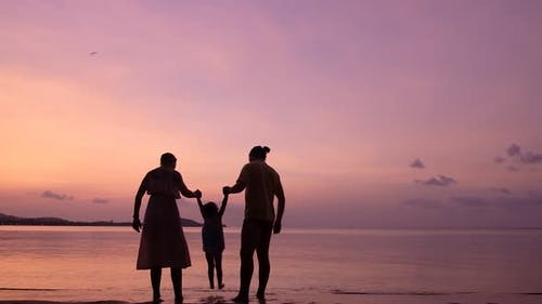 Family of Three Playing on the Tropical Beach at the Sunset Time. Happy Family Concept.