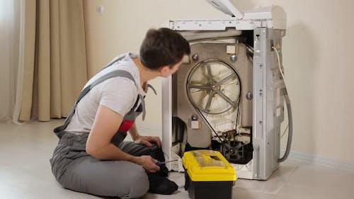 Master Opens Back Panel of Broken Washing Machine