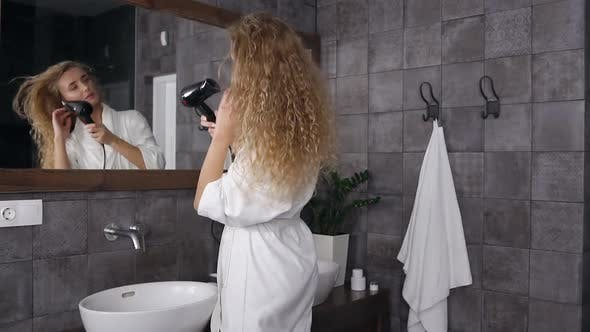 Cover Image for Young Woman in white Robe Standing Near Mirror in the Bathroom and Drying Her Curly Hair