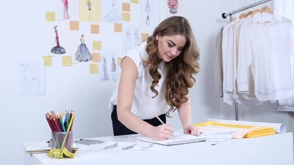 Cover Image for Fashion Designer Draws Sketches for a New Collection in Her Workshop