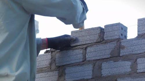 Schließen Schuss auf die Hände des Maurers, Männlicher Freiwilliger legt Ziegel mit Zement in die Mauer