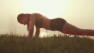 The Athlete Does Pushups at Sunset By the Sea