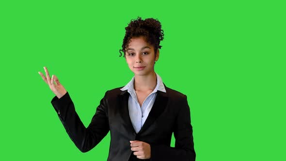 African AMerican Businesswoman Talking on Camera and Pointing at a Blank Space on a Green Screen
